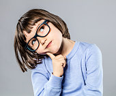 thoughtful beautiful little girl with serious eyeglasses holding her head to imagine, think, hesitate or have an intelligent idea or solution, grey background studio