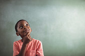 Thoughtful boy standing against greenboard in classroom