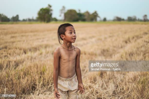 Thoughtful Boy Looking Away While Standing On Field At Farm