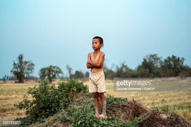 Thoughtful Boy With Arms Crossed Standing On Field Against Sky At Farm