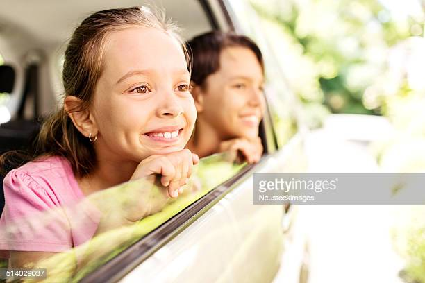 Pensive frère et Soeur regardant par la fenêtre de la voiture