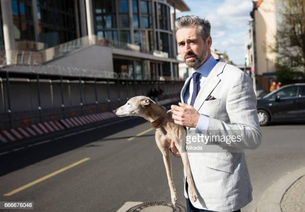 Thoughtful businessman carrying dog while standing on city street