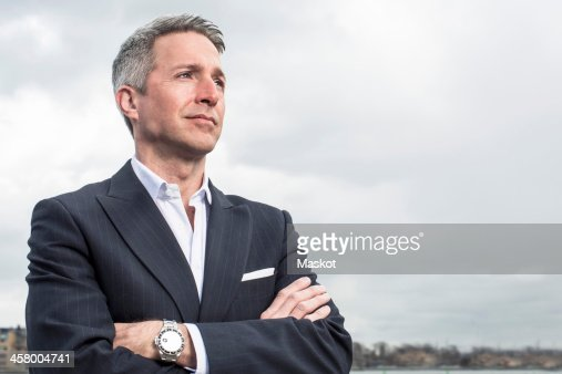 Thoughtful businessman looking away while standing arms crossed against cloudy sky