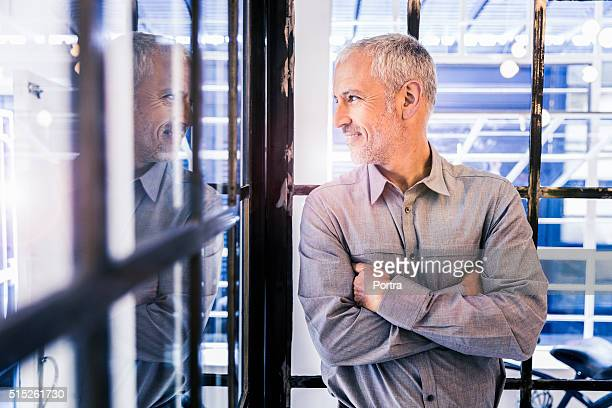 Thoughtful businessman looking out through glass wall