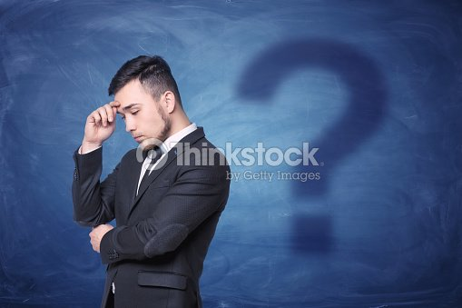 thoughtful businessman on blue chalkboard background with a shadow