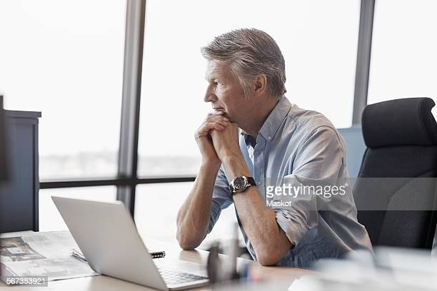 Thoughtful businessman sitting at desk in office