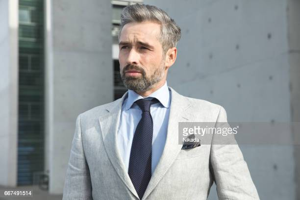 Thoughtful businessman standing against wall