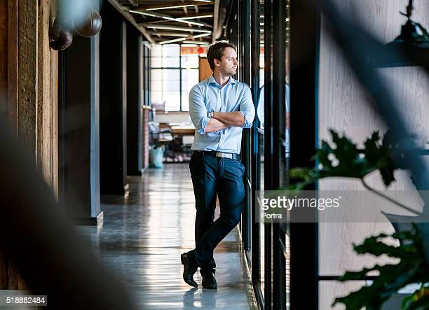 Thoughtful businessman standing arms crossed in office