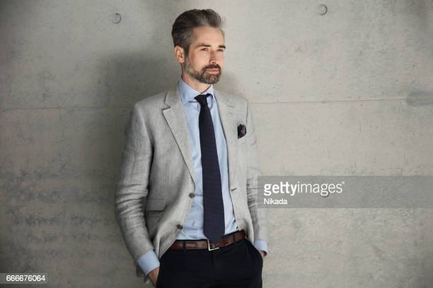 Thoughtful businessman standing with hand in pocket against wall