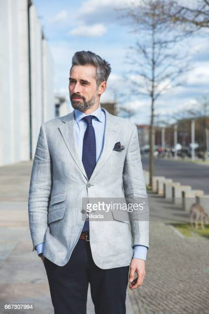 Thoughtful businessman standing with hand in pocket on city side walk