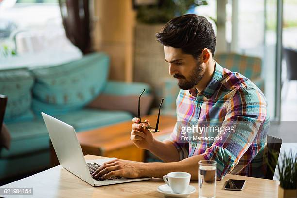 Thoughtful businessman using laptop and focusing on his work.