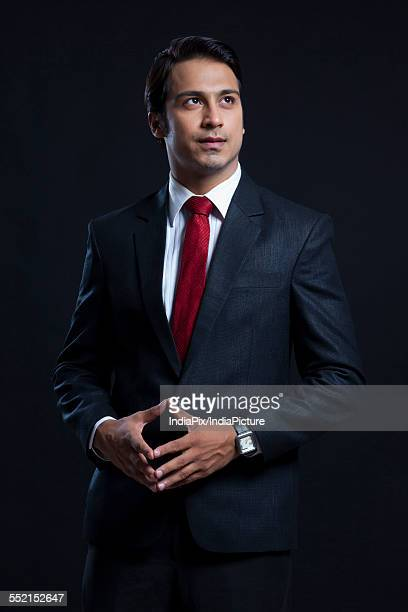 Thoughtful businessman with hands clasped standing against black background