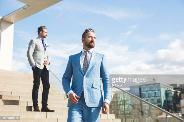 Thoughtful businessmen standing on steps against sky