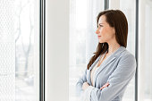 Thoughtful businesswoman looking through window in office