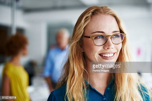 Thoughtful businesswoman smiling in office
