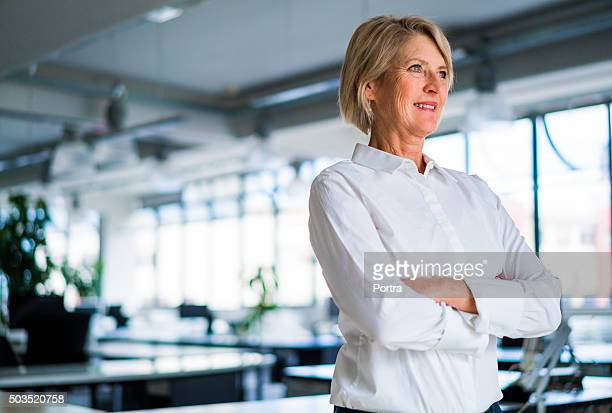 Thoughtful businesswoman standing arms crossed