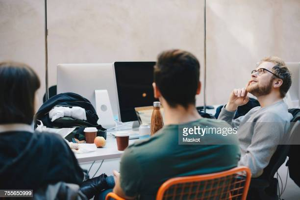 Thoughtful computer programmer sitting with colleagues in office