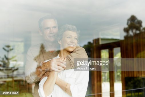 Thoughtful couple looking through window