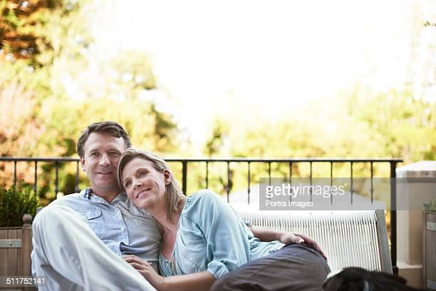 Thoughtful couple sitting at balcony