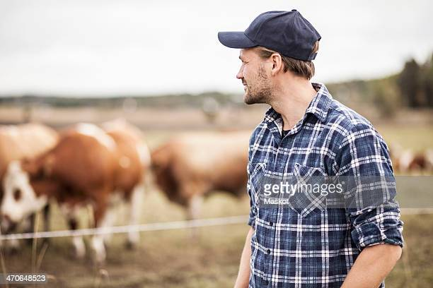 Thoughtful farmer standing on field while animals grazing in background