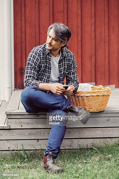 Thoughtful farmer with wicker basket holding mobile phone while sitting on porch at yard