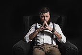 thoughtful fashionable businessman sitting in armchair and looking at camera, isolated on black