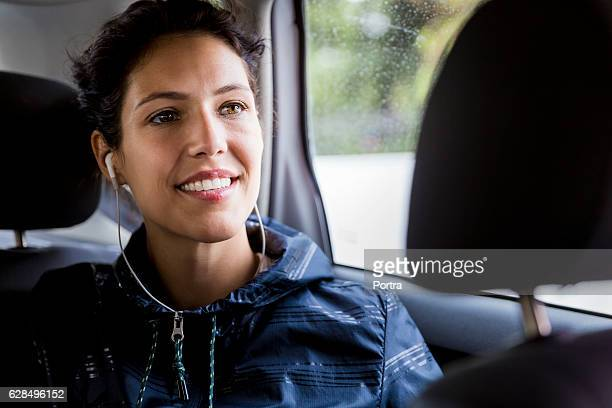Thoughtful female athlete sitting in car