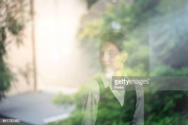 窓から見られる思慮深い女性起業家