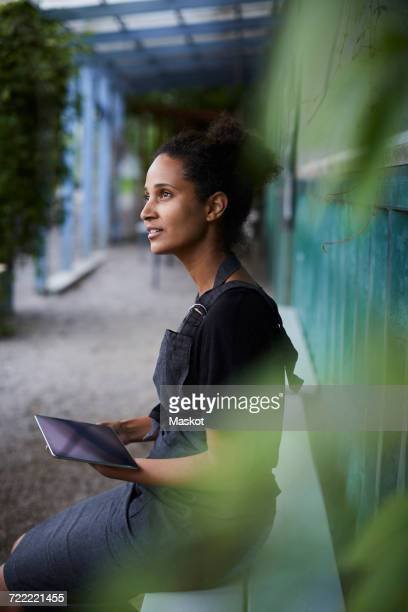 Thoughtful female gardener holding tablet computer in shade
