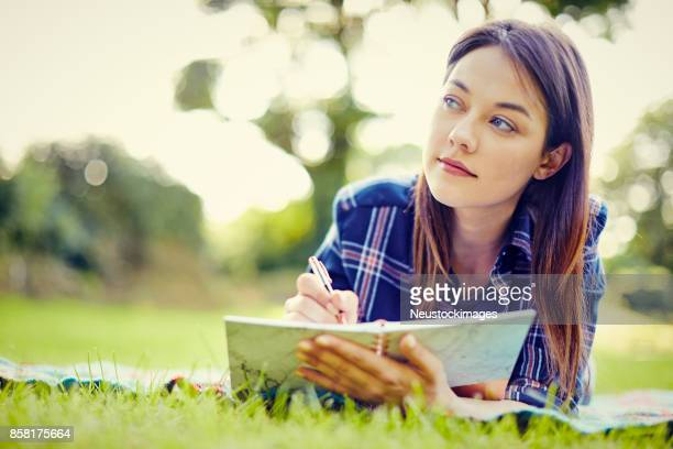 Thoughtful female hipster writing in diary while lying in park