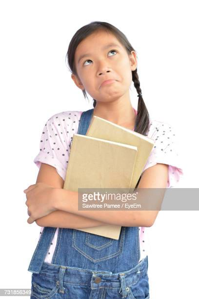 Thoughtful Girl Holding Books Looking Up While Standing Against White Background