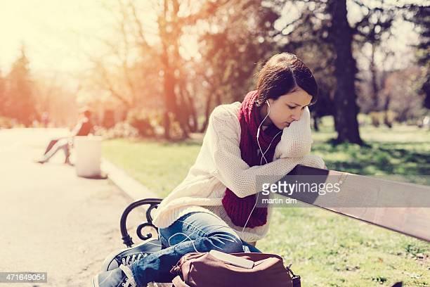 Pensierosa ragazza ascoltando musica su panca