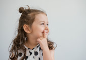 Close up portrait of a cute little girl thinking, studio shot