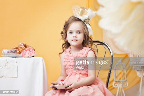 Pensativa joven posando con una porción de torta en interiores retro : Foto de stock