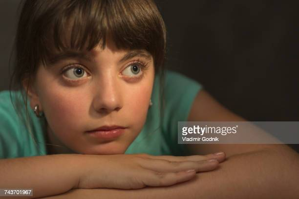 Thoughtful girl resting while looking away against gray background