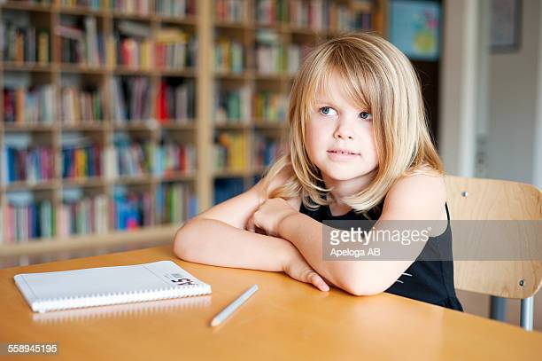 Thoughtful girl sitting at desk in classroom