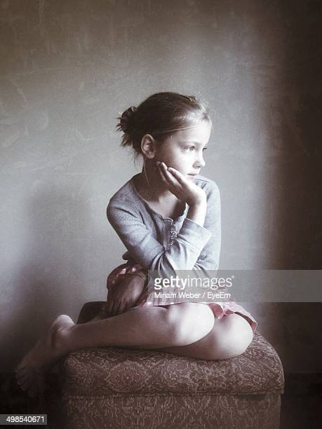 Thoughtful girl with hand on chin sitting on footstool