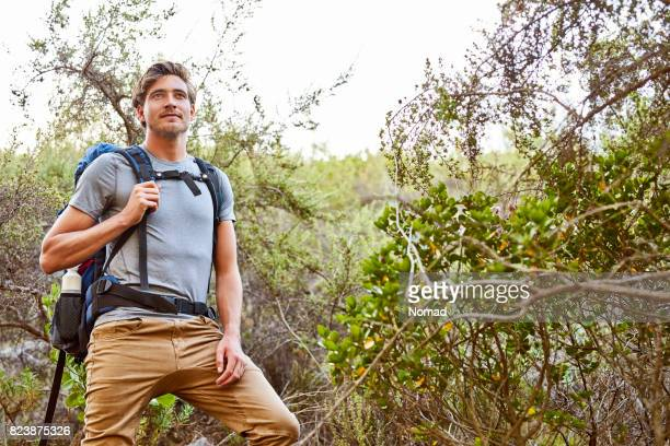 Thoughtful hiker looking away in forest