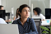 Thoughtful indian business woman looking away feeling bored pensive thinking of problem solution in office with laptop, serious hindu employee searching new ideas at work unmotivated about dull job