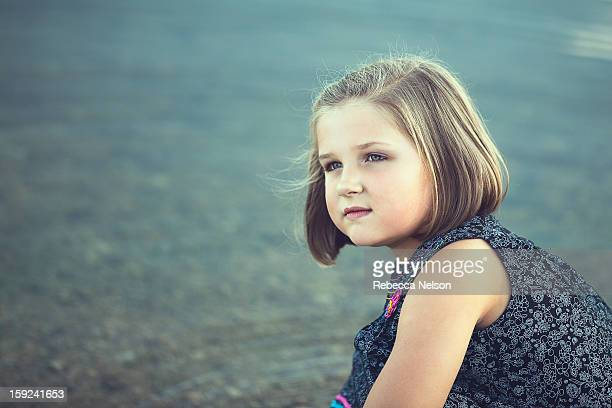Thoughtful little girl in front of lake