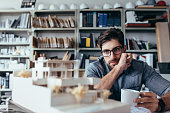 Thoughtful male designer in office looking at model with cup of coffee. Young male architect taking break from work.