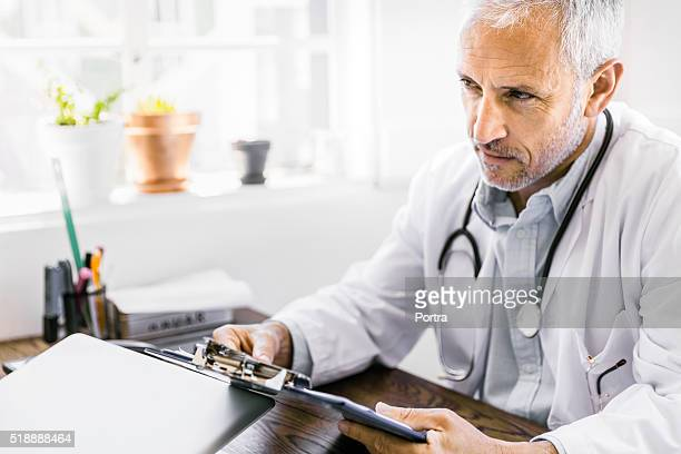 Thoughtful male doctor holding clipboard at desk