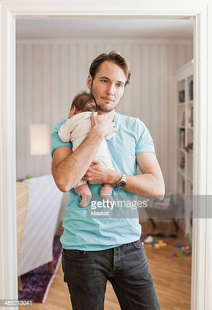 Thoughtful man carrying baby at doorway