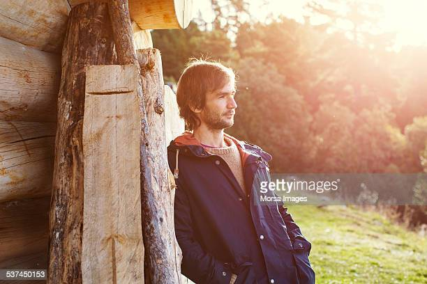 Thoughtful man leaning on log cabin