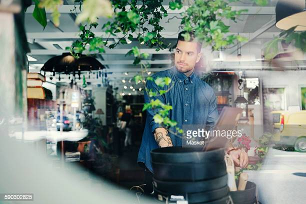 Thoughtful man looking away while working in shop seen through glass window