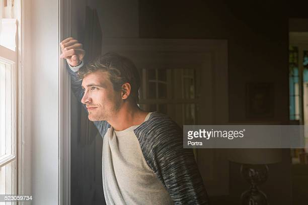 Thoughtful man looking through window at home