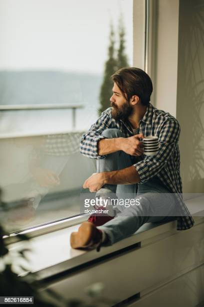 Thoughtful man relaxing on window sill during his coffee time.