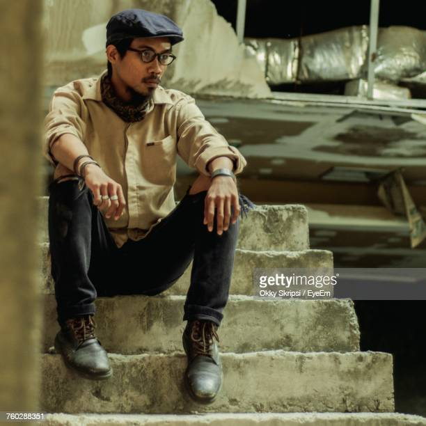 Thoughtful Man Sitting On Steps Of Abandoned Building