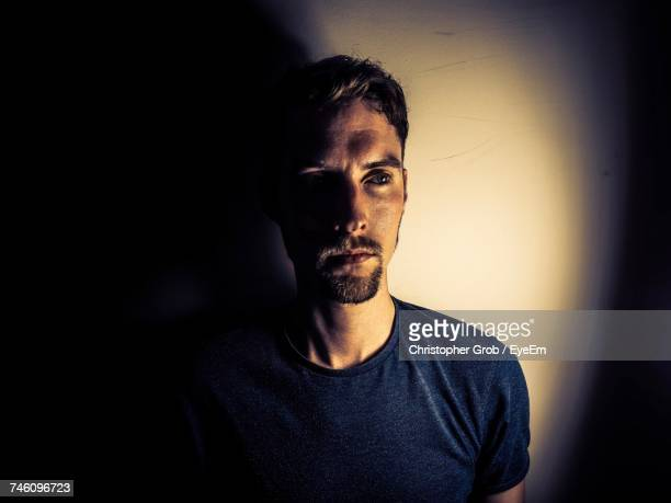 Thoughtful Man Standing Against Wall In Room