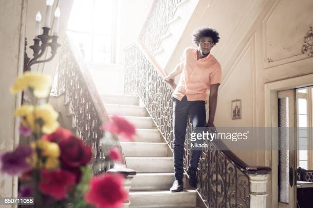 Thoughtful man standing on steps at home
